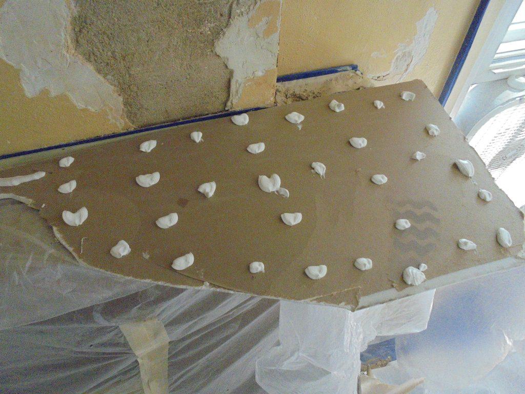 Preparing a piece of board to go over the brick